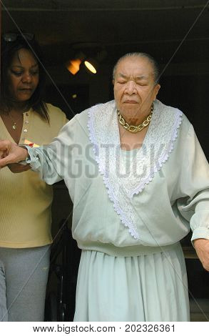 JULY 15, 2006, SEATTLE, WA, CIRCA: African american female caregiver helping a senior get into a car from a nursing home to go to church on sunday.