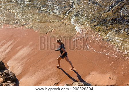 Girl athlete overhead unidentified morning training running along beach ocean wave shoreline.