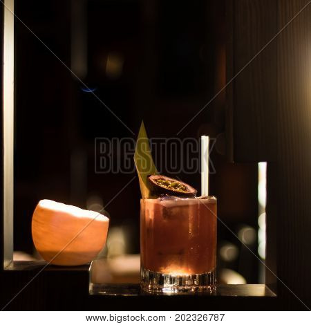 Fruit cocktail lit by candle and garnished with fig and leaf. Alcoholic drink in old fashioned glass in bar