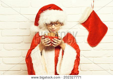 young cute santa claus boy with glasses in red sweater and new year hat with decorative christmas or xmas stocking or boot hold and sniff chocolate chip cookies in bowl on white brick wall background