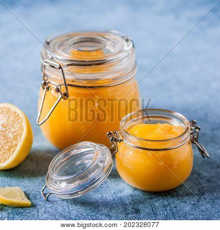 Lemon Curd In Jars Over Blue Background