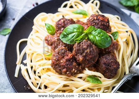 Pasta linguine with meatballs in tomato sauce. Close up.