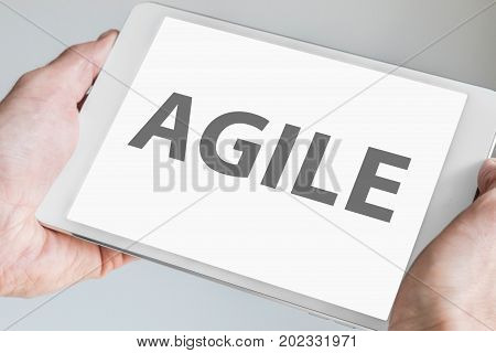 Agile text displayed on touchscreen of modern tablet or smart device. Concept of modern software development methodology for smartphones.