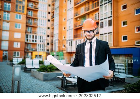 Engineer In Front Of Modern Building With Plan Looking At Blueprint