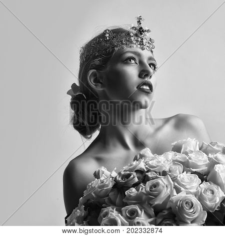 princess woman with luxury crown with diamond and gem has bare shoulders hold rose bouquet black and white