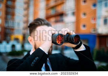 Handsome Businessman With Binoculars Spying On Competitors Outdoors