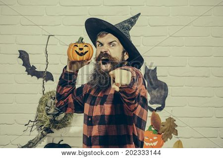 Halloween hipster shouting and pointing finger with anger. Man with pumpkin in witch hat. Mystery and horror concept. Holiday celebration symbols on beige brick wall. Trick or treat.