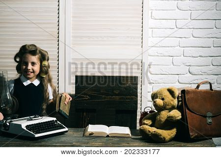 Small girl with curler in hair. Child with briefcase and alarm clock. Education and childhood. Kid choose career and typing. Little baby secretary with bear and book.