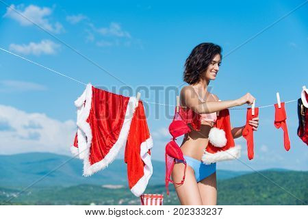 Christmas woman with happy face outdoor. New year girl on sunny blue sky. Santa claus girl hanging clothes for drying. Laundry and dry cleaning. Xmas red costume on rope with pin.