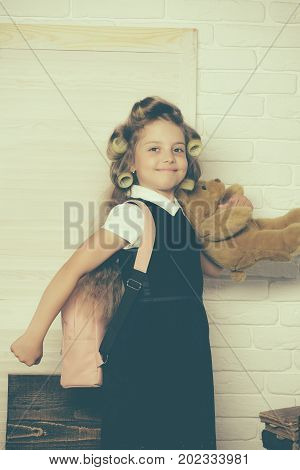 Child play in school. Little baby with bear. Kid with school bag. Education and childhood. Small girl with curler in hair.