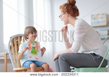 Boy Showing Picture To Counselor