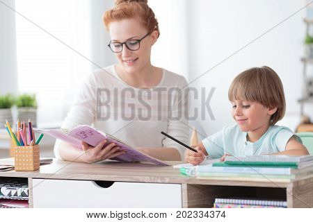 Boy Doing Exercises From Workbook