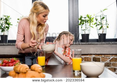 Mother Feeding Daughter At Breakfast