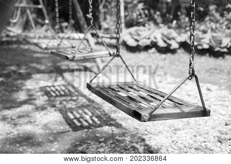 Empty swings on playground.wings in city park. Empty chain swings in summer kids children playground.