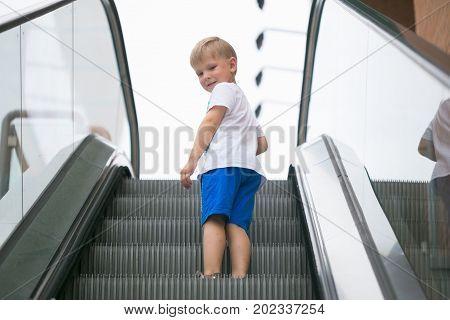 Little boy riding an escalator one dangerous