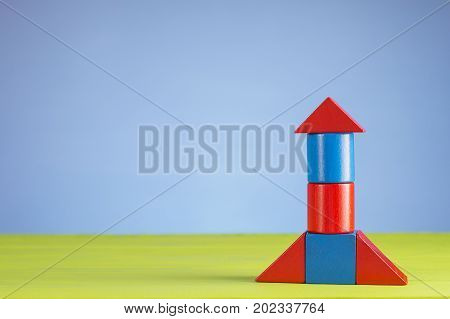 Abstract rocket from wooden blocks with copy space. Wooden puzzle in rocket shape start up concept.