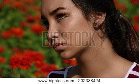 Hispanic Female Teenager Wondering Near Red Flowers