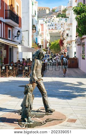 Ibiza Spain - June 10 2017: Bronze sculpture honours hippie culture in Ibiza Town. The sculpture is the work of Catalan sculptor Cio Abelli. The bronze sculpture is based on a legendary photograph taken by Toni Riera of a hippie father and his daughter