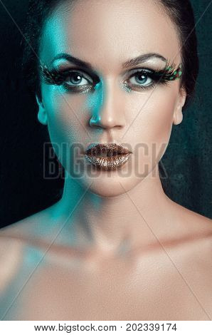 beauty portrait of a woman with a fake big green eyelashes feather emerald green side light