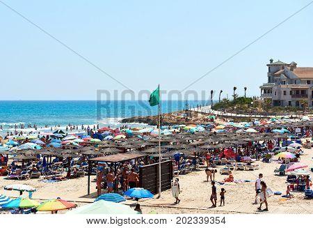 Orihuela Spain - August 17 2017: People enjoying the summer on the beach of La Zenia Orihuela coast. Costa Blanca. Spain