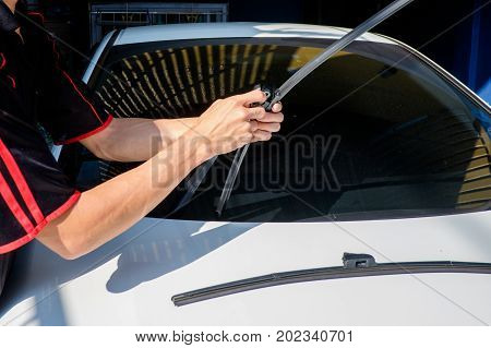Man is changing windscreen wipers on a car Asian man installing new windshield wipers by himself at home