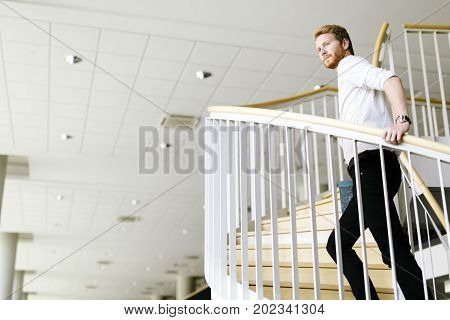 Business visionary represented by a man climing stairs and thinking