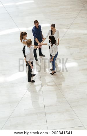 Business teamwork. People with joined hands. Union. Top View