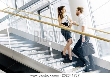 Business colleagues talking on stairs and flirting
