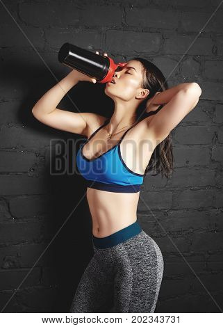 Beautiful young fitness woman in fashion sports clothes near black wall. Girl hold sport nutrition shaker. Fitness model with sexy body perfect shape