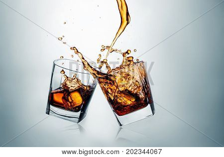 Two whiskey glasses clinking together on gray studio background