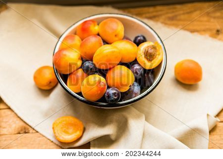 Top view of summer stone fruits in bowl on cloth heathy diet concept