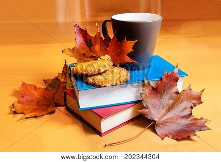 Tea with cookies book and autumn leaves