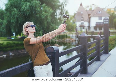 Woman capturing herself with small personal camera in a park