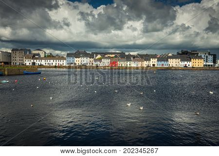 Galway Ireland - August 5 2017: Closeup of lIne of colorful houses of The Long Walk quay under enormous black and grey clouds and with dark blue water of the port in front. Some small boats and seagulls.