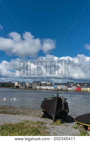 Galway Ireland - August 5 2017: Portrait of enormous white cloudscape in blue sky over section of The Long Walk quay. Up front black boat on shore. Dark water in between with white swans.