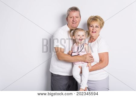 grandmother and geandfather with grandchild on light background