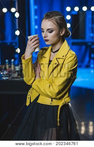 attractive girl with makeup in yellow leather jacket holding paper cup