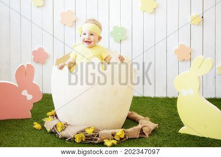 photo of ittle girat the eggshell and rabbits around
