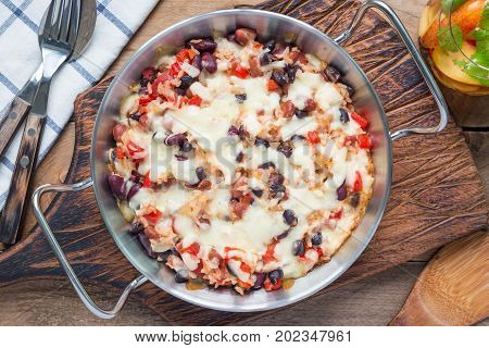 Baked rice casserole with different kinds of beans cheese and paprika in metal baking dish horizontal top view