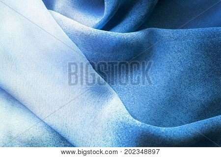 Abstract draped dark and light blue silk as a background