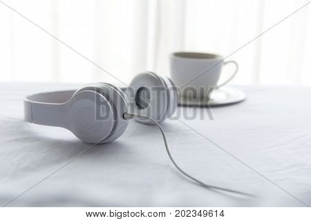 Morning music background. Coffee in white bed sheet duvet and pillow messed up. Music and Lifestyle Concept.