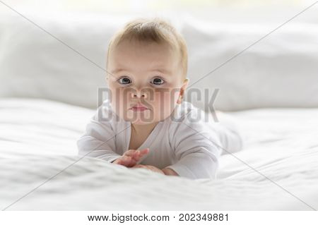 A Cute happy 7 month baby girl in diaper lying and playing