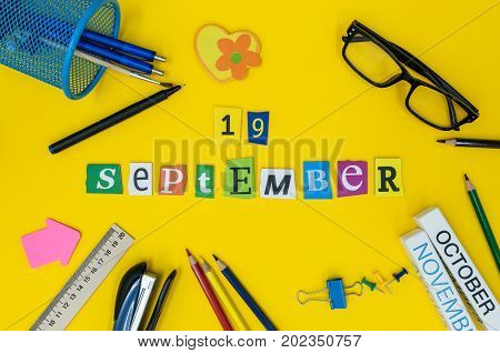 September 19th. Day 19 of month, Back to school concept. Calendar on teacher or student workplace background with school supplies on yellow table. Autumn time.