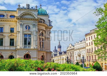 Krakow/Poland- August 15, 2017: Cityscape of old town, part view of Juliusz Slowacki Theatre building, Szpitalna street and town hall on a sunny summer day with blue sky and blooming tea rose bushes