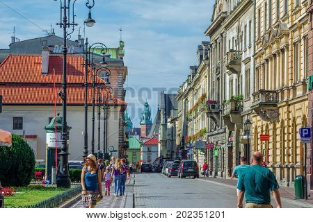 Krakow/Poland- August 15, 2017: Cityscape of old town, tourists and citizens walking on Szpitalna street, view of town hall on background, sunny summer day with blue sky