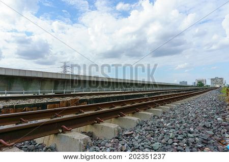 side view of railway track and crushes rock near the bridge with blue sky and cloudy background. milestone concept