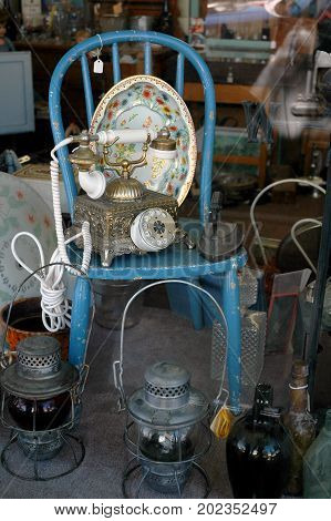 Antiques and other old things for sale in a shop window.