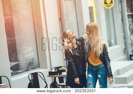 It is funny walk with best friend! Two beautiful women walking outdoor hugging and laughing on autumn street. Fashion urban girls spending weekend talking at sunset near a cafe.