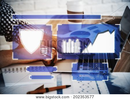 Side view of male hands using laptop placed at workplace with coffee cup paperwork supplies other items and digital antivirus screen