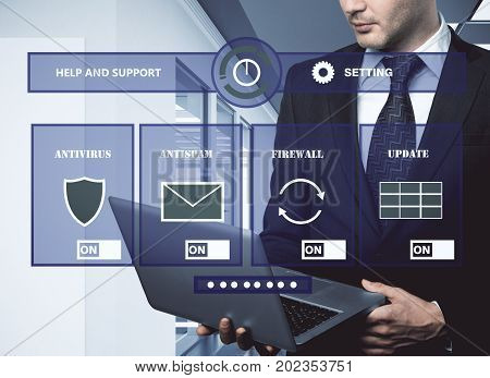 Handsome businessman using laptop in office interior with abstract antivirus screen. Future concept